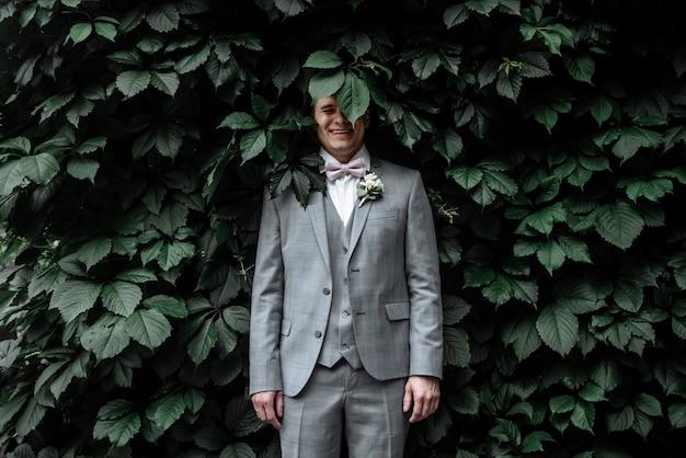 Szczęśliwy pana młodego w garniturze ślubu w dniu ślubu w ogrodzie na ścianie bluszczu