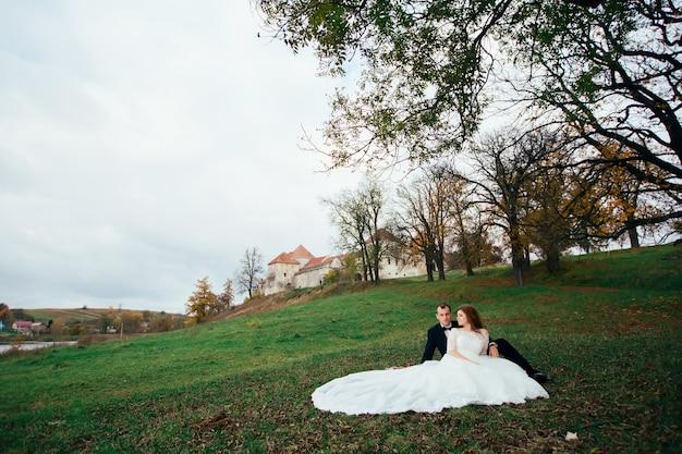 Szczęśliwy państwo młodzi przy parkiem w ich dniu ślubu