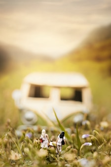 Szczęśliwy para pasażer z rocznika miniaturowym samochodem dostawczym w naturze podróży i wakacje pojęcie, płytka głębia pole skład.