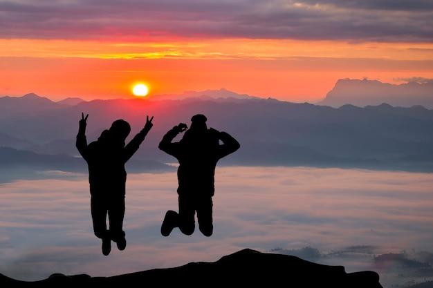 Szczęśliwy pary doskakiwanie na górze na wschodu słońca czasie. ludzie bawią się na zewnątrz. pojęcie przyjaznej rodziny.