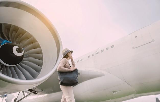 Szczęśliwy pasażer podróży asia kobieta stojąc przed samolotem.