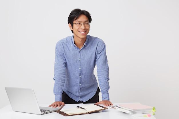 Szczęśliwy pewnie azjatyckiego młodego biznesmena w okularach, stojąc i pracując przy stole z laptopem i notebookiem na białym tle nad białą ścianą