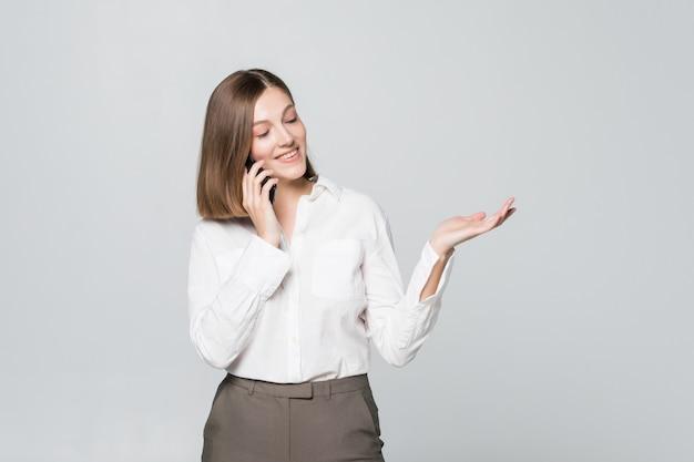 Szczęśliwy pewnie bizneswoman opowiada na telefonie komórkowym odizolowywającym
