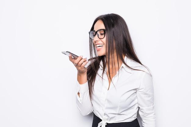 Szczęśliwy pewnie bizneswoman rozmawia przez telefon komórkowy na telefon głośnomówiący na białym tle