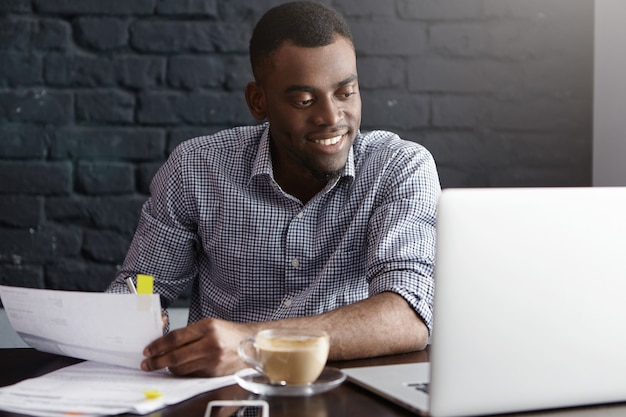 Szczęśliwy pewnie młody biznesmen afroamerykański w wizytowym wypełnianiu dokumentów