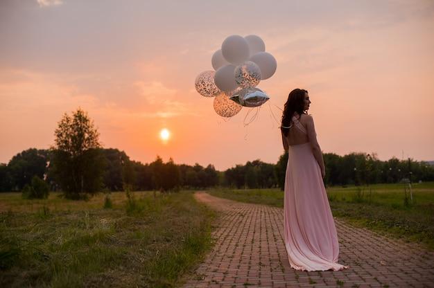 Szczęśliwy piękna kobieta w ciąży w różowej długiej sukni chodzenie z balonów powietrzem w zielony p