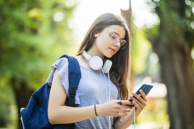 Szczęśliwy piękna młoda dziewczyna kaukaska z zielonym inteligentny telefon na zewnątrz w słoneczny letni dzień sms-y i uśmiechnięty.