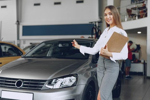 Szczęśliwy piękna młoda kobieta dealer samochodowy w salonie