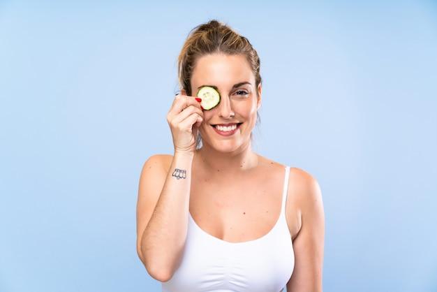 Szczęśliwy piękna młoda kobieta trzyma plasterki ogórka