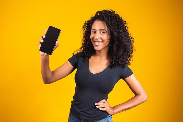 Szczęśliwy piękna młoda kobieta z afro włosów trzymając telefon komórkowy pusty ekran na żółtym tle.