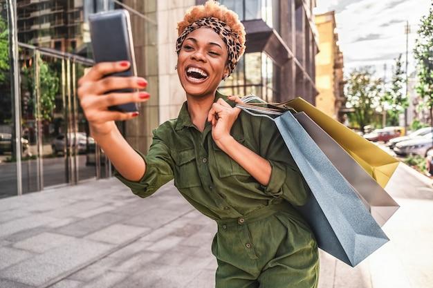 Szczęśliwy piękny afro american kobieta spacerując trzymając torby na zakupy i biorąc selfie na telefon
