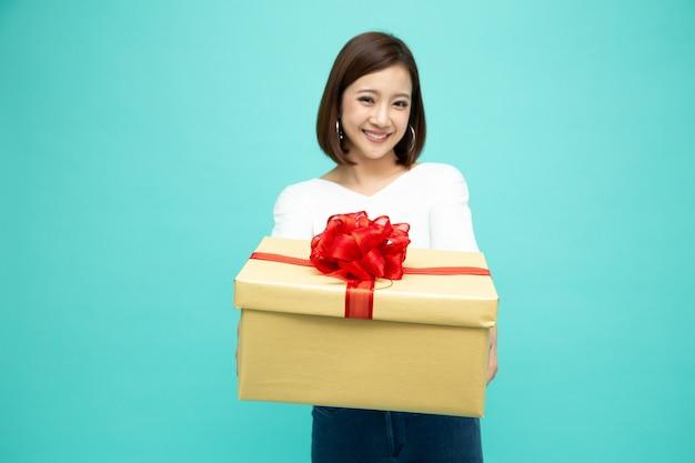 Szczęśliwy piękny asian kobieta uśmiech i trzymając pudełko na białym tle na białej ścianie.
