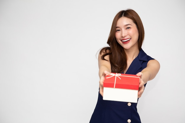 Szczęśliwy piękny azjatycki uśmiech kobieta z czerwonym szkatułce na białym tle.