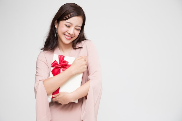 Szczęśliwy piękny azjatykci kobieta uśmiech z czerwonym prezenta pudełkiem. zakochane nastolatki, otrzymujące prezenty od kochanków. koncepcja nowego roku, świąt bożego narodzenia i walentynki