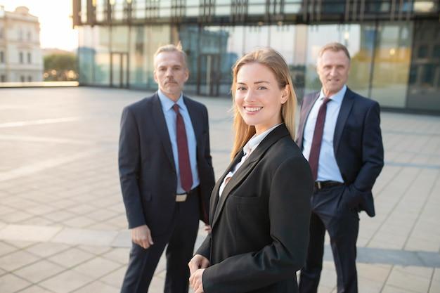 Szczęśliwy piękny biznes kobieta ubrana w garnitur, stojąc na zewnątrz i patrząc na kamery. mężczyzna stojących w tyle kolegów biznesowych. koncepcja zespołu biznesowego