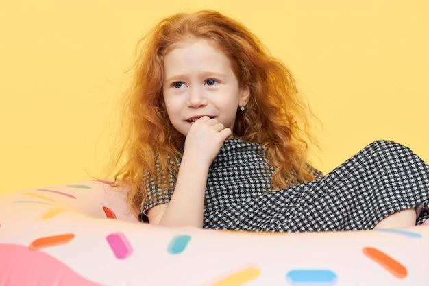 Szczęśliwy piękny rudowłosy dziecko płci żeńskiej w letniej sukience trzymając rękę na ustach, leżąc na różowym gumowym pierścieniu