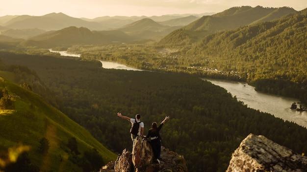 Szczęśliwy pieszy mężczyzna i kobieta z plecakami z podniesionymi rękami na szczyt, z widokiem na dolinę ze szczytu góry. koncepcja podróży i podróż w góry na wakacje