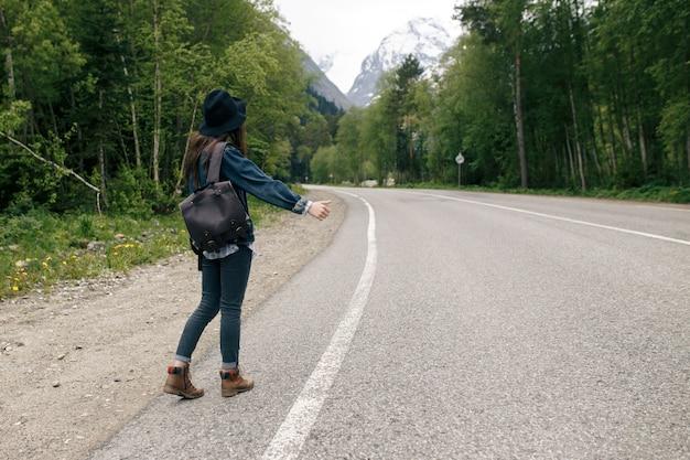 Szczęśliwy plecak dziewczyna na tle drogi i lasu, czas relaksu na wakacyjnej podróży koncepcyjnej, kolor tonu vintage i nieostrość