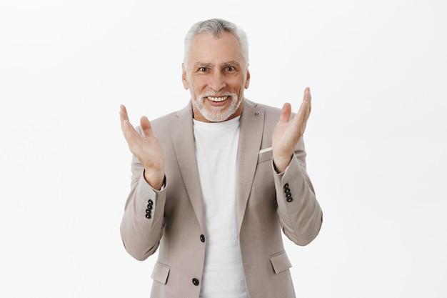 Szczęśliwy pochlebny starszy mężczyzna w garniturze klaszcze w dłonie i wygląda podekscytowany