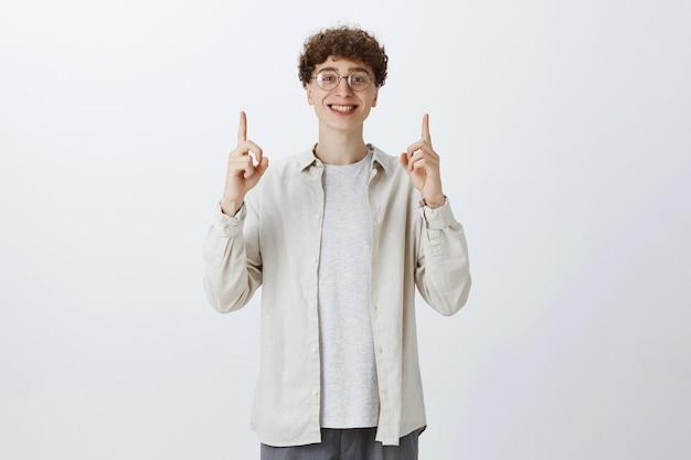 Szczęśliwy pod wrażeniem nastoletni facet pozuje przy białej ścianie