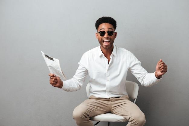 Szczęśliwy podekscytowany afrykański mężczyzna trzyma gazetę