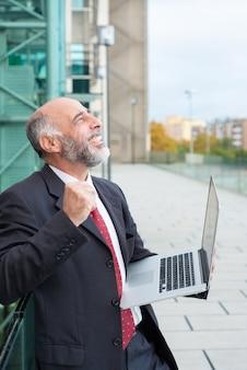 Szczęśliwy podekscytowany dojrzały lider biznesu z laptopem