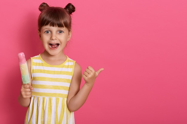 Szczęśliwy podekscytowany dzieciak z lodami z szeroko otwartymi ustami, wskazując kciukiem na bok, zabawna dziewczyna z węzłami, miejsce na reklamę.