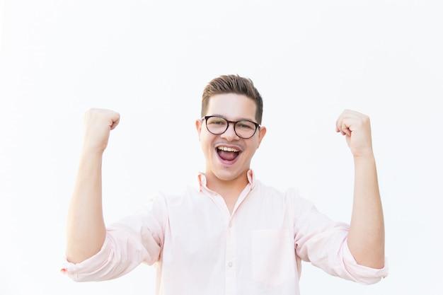 Szczęśliwy podekscytowany facet krzyczy z radości w okularach