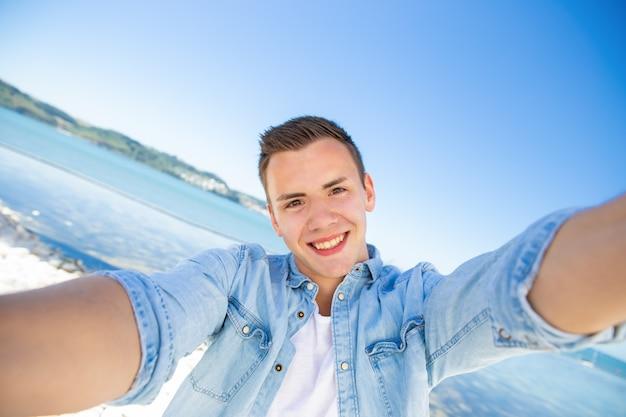 Szczęśliwy podekscytowany facet turystyczny biorąc selfie na morzu
