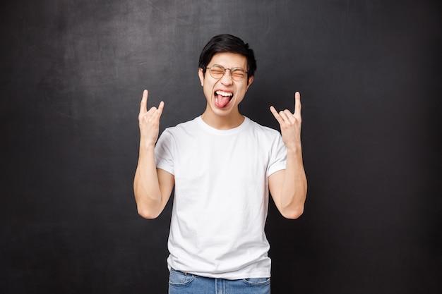 Szczęśliwy podekscytowany i towarzyski azjatycki facet w okularach i koszulce, zabawny pokaz języka zamknął oczy zrelaksowany i wykonał rock-n-rollowy heavy metal jako słuchanie niesamowitej piosenki,