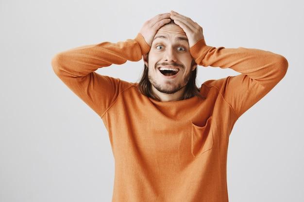 Szczęśliwy podekscytowany mężczyzna reaguje na wspaniałe wieści, zdumiony trzyma ręce za głowę