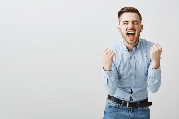 Szczęśliwy podekscytowany mężczyzna śpiewa ulubioną piosenkę, tańczy do muzyki w słuchawkach bezprzewodowych