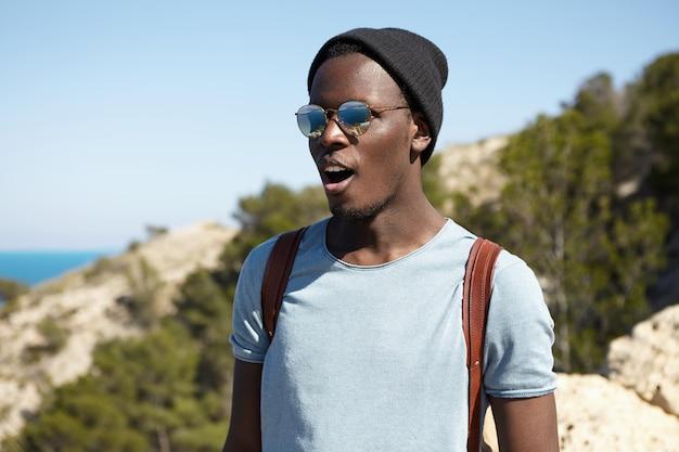 Szczęśliwy podekscytowany młody afroamerykanin podróżnik w stylowych odcieniach i nakryciu głowy wyglądający na oszołomionego, z szeroko otwartymi ustami, stojąc wysoko w górach i podziwiając piękny widok poniżej