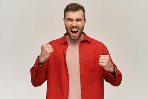 Szczęśliwy podekscytowany młody brodaty mężczyzna w czerwonej koszuli krzyczy i świętuje zwycięstwo nad białą ścianą patrząc na przód
