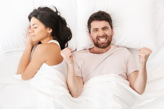 Szczęśliwy, podekscytowany młody człowiek leży w łóżku pod kocem w pobliżu śpiącej kobiety, wykonując gest zwycięzcy