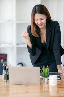 Szczęśliwy podekscytowany pomyślny bizneswoman triumfuje podczas gdy pracujący w nowożytnym biurze.