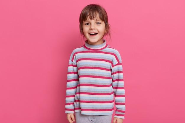 Szczęśliwy podekscytowany przedszkolak dziewczyna ubrana w pasiastą koszulę w stylu casual, pozowanie na białym tle nad różową ścianą