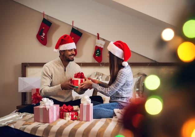 Szczęśliwy podekscytowany przystojny para, dając sobie prezenty świąteczne, siedząc na łóżku w swetry i santa kapelusze.