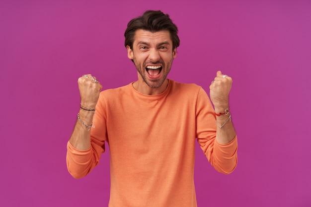 Szczęśliwy, podekscytowany wyglądający facet z brunetką i włosiem. ubrana w pomarańczowy sweter z podwiniętymi rękawami. zaciskaj pięści i świętuj zwycięstwo