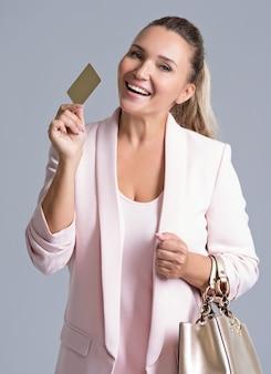 Szczęśliwy podekscytowany zaskoczony młoda kobieta z kartą kredytową na białym