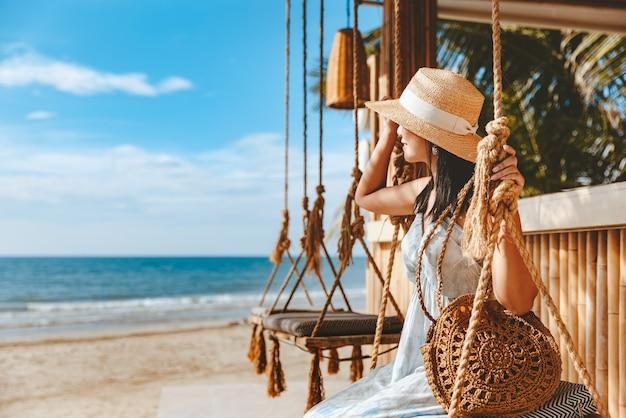 Szczęśliwy podróżnik azjatycka kobieta z kapeluszem i sukienką relaksuje się na huśtawce w kawiarni na plaży, koh chang, tajlandia
