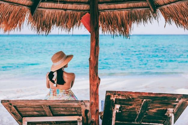 Szczęśliwy podróżnik azjatycka kobieta z kapeluszem relaks na plaży krzesła w koh lipe, satun, tajlandia