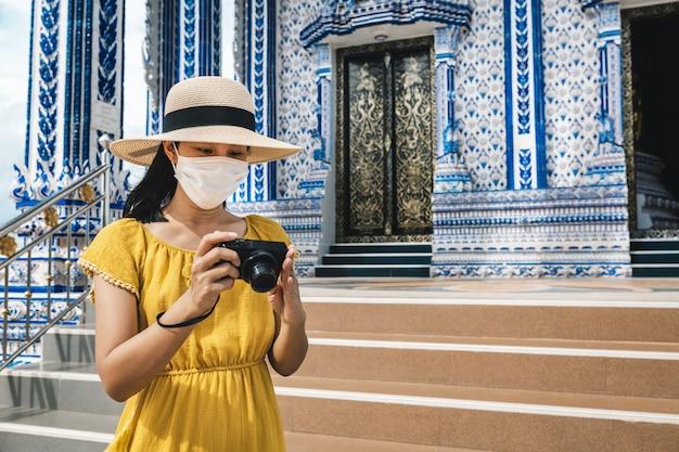 Szczęśliwy podróżnik azjatycka kobieta z maską i kamerą zwiedzanie świątyni wat pak nam khaem nu, chanthaburi, tajlandia