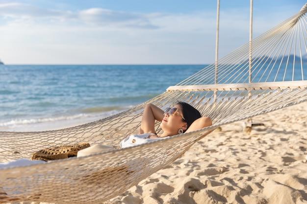 Szczęśliwy podróżnik azjatykcia kobieta z kapeluszem relaks w hamaku na plaży w koh chang, trad, tajlandia
