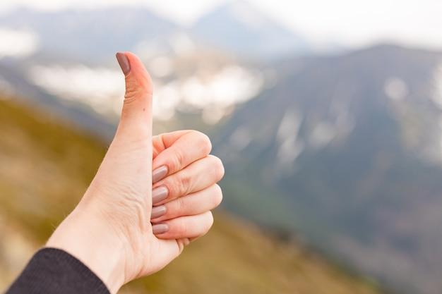 Szczęśliwy podróżnik fimale pokazując kciuk w góry wiosną, strzał z punktu widzenia