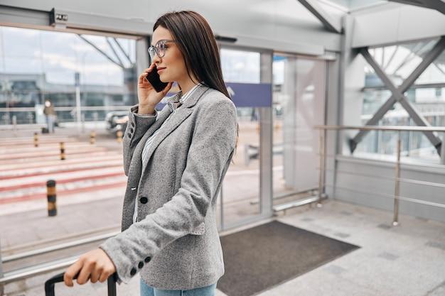 Szczęśliwy podróżnik kaukaski kobieta w terminalu lotniska z bagażem