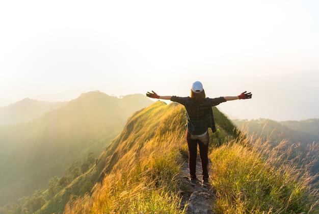 Szczęśliwy podróżnik kobieta podniosła ramiona na szczycie góry, poczuć wolność i cieszyć się naturą.