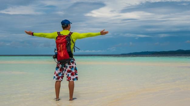 Szczęśliwy podróżnik na white sand bank podczas odpływu na wyspie kri. raja ampat, indonezja, papua zachodnia.