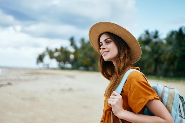 Szczęśliwy podróżnik odpoczywa na wyspie wśród palm i plecaka