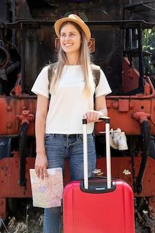 Szczęśliwy podróżnik ono uśmiecha się przy dworcem